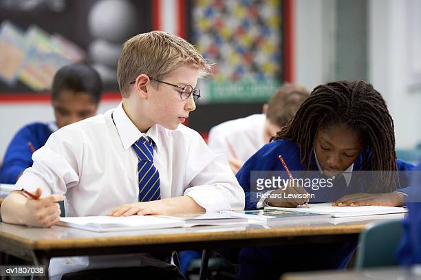 Primary Schoolboy Sitting Next to a Schoolboy in a Classroom Watching Him Writing in an Exercise Book