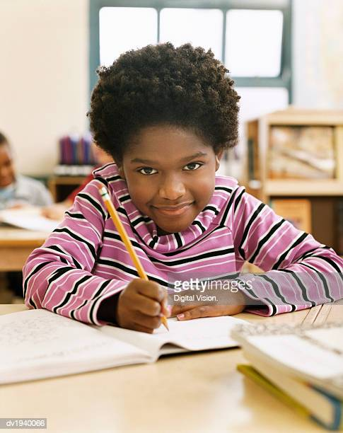 Primary Schoolboy Writing in His Exercise Book in a Classroom