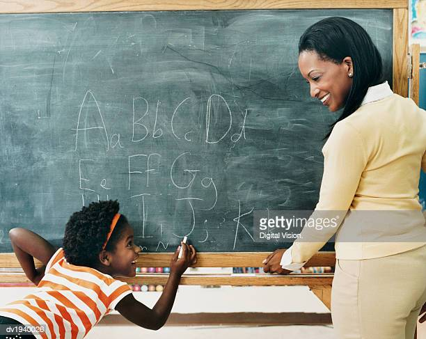 Primary Schoolgirl in a Classroom Writing on a Blackboard and a Teacher Watching