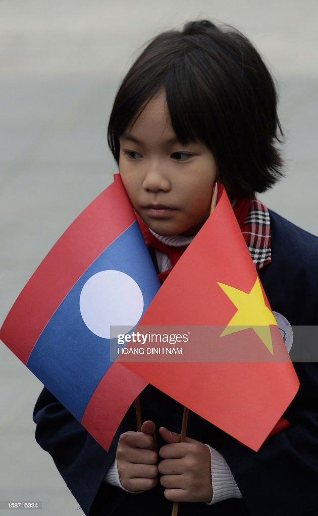 A primary shool girl holds Vietnamese (R) and Lao flags prior to the arrival of the visiting Lao President Choummaly Sayasone (not pictured) for a welcoming ceremony at the presidential palace in Hanoi on December 26, 2012. The three-day visit by Lao leader is part of celebrations marking the 50th anniversary of the diplomatic relations between two Southeast asian communist nations . AFP PHOTO/HOANG DINH Nam