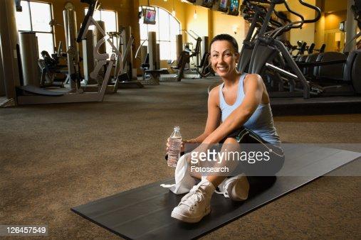 Prime adult Caucasian female sitting on mat on gym floor.