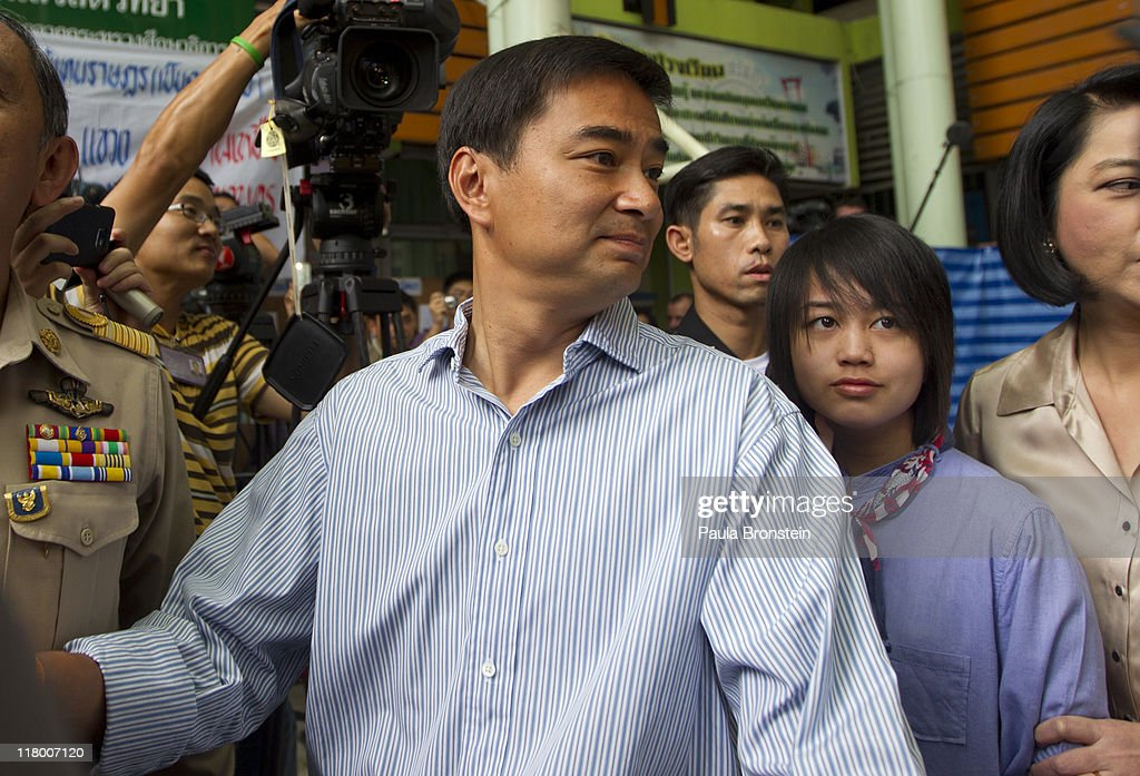 Prime Minister Abhisit Vejjajiva tries to leave the polling booth along side his wife Pimpen and daughter Prang after voting July 3rd, 2011 in Bangkok, Thailand as Thai's vote in the country's 4th election in 7 years. The vote pits Prime Minister Abhisit Vejjajiva's Democrat's against Thaksin's younger sister, Yingluck Shinawatra, who has the full support of the red shirt followers of fugitive former premier Thaksin Shinawatra, ousted in a 2006 coup.