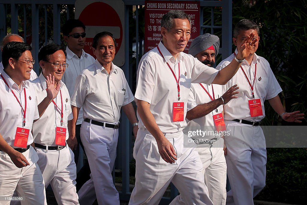 Prime Minister and the Secretary General of the People's Action Party, <a gi-track='captionPersonalityLinkClicked' href=/galleries/search?phrase=Lee+Hsien+Loong&family=editorial&specificpeople=3911578 ng-click='$event.stopPropagation()'>Lee Hsien Loong</a> (C) arrives at a polling station on May 7, 2011 in Singapore. 2.21 million voters are expected to visit polling stations across Singapore, in the countries 11th elections since independence. The 2011 general election has been the most contested in Singapore's history with 82 seats out of 87 being contested. In 2006 the People's Action Party (PAP) received 66.6 per cent of the vote.