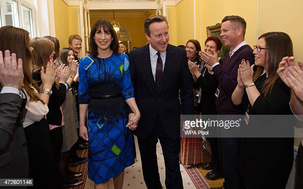 Prime Minister David Cameron and his wife Samantha Cameron are applauded by staff upon entering 10 Downing Street as he begins his second term as...