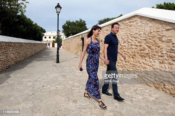Prime Minister David Cameron and his wife Samantha Cameron walk hand in hand through the centre of Santa Gertrudis at the beginning of their holiday...