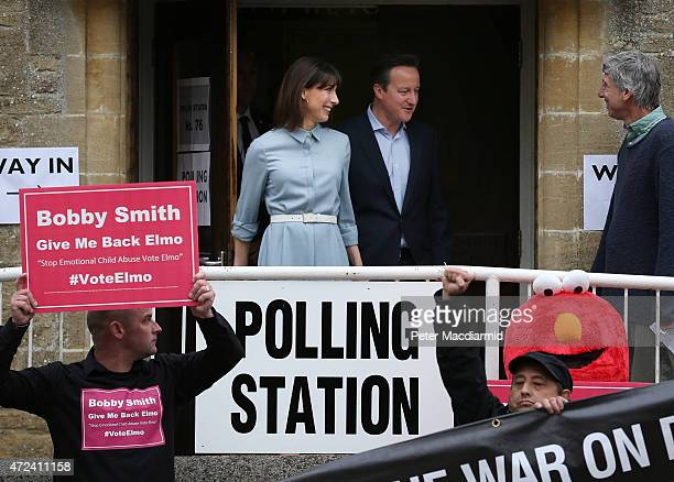 Prime Minister David Cameron and his wife Samantha pass demonstrators as they leave a polling station after casting their vote in the general...