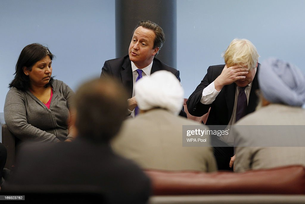 Prime Minister David Cameron and London Mayor Boris Johnson are seen during a meeting with members of the local community during a visit to Woolwich...