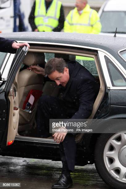 Prime Minister David Cameron gets out of a car prior to boarding a British Airways flight to Zurich at Heathrow Airport London