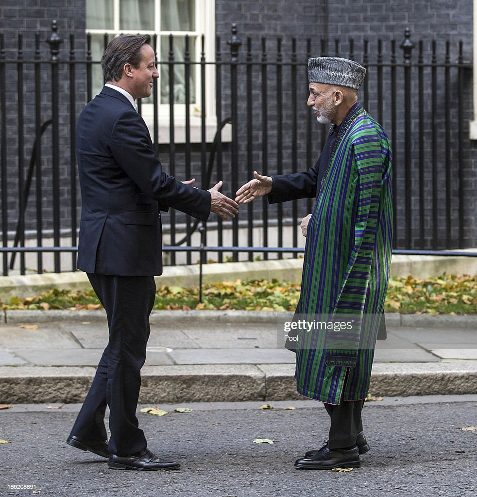 Prime Minister <a gi-track='captionPersonalityLinkClicked' href=/galleries/search?phrase=David+Cameron+-+Politicus&family=editorial&specificpeople=227076 ng-click='$event.stopPropagation()'>David Cameron</a> greets the President of Afghanistan <a gi-track='captionPersonalityLinkClicked' href=/galleries/search?phrase=Hamid+Karzai&family=editorial&specificpeople=121540 ng-click='$event.stopPropagation()'>Hamid Karzai</a> on the steps of 10 Downing Street for the start of tri lateral talks which included the Pakistani Prime Minister Nawaz Sharif on October 29, 2013 in London, England.