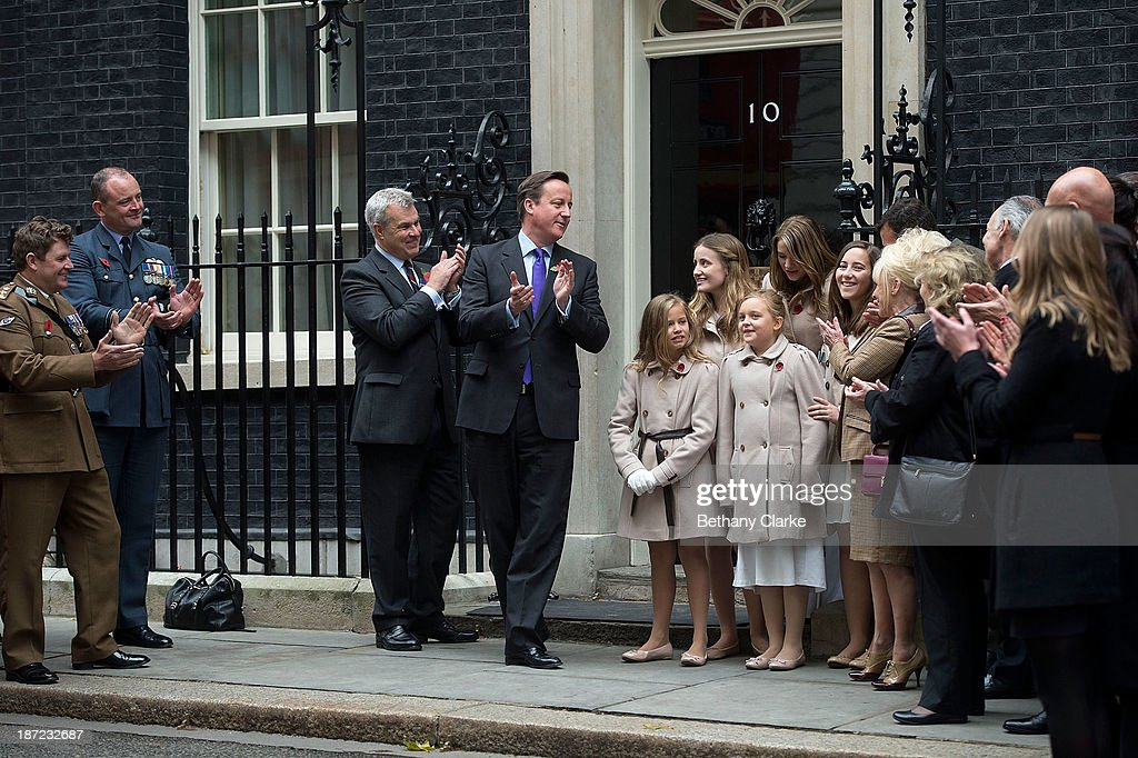 Prime Minister, <a gi-track='captionPersonalityLinkClicked' href=/galleries/search?phrase=David+Cameron+-+Politician&family=editorial&specificpeople=227076 ng-click='$event.stopPropagation()'>David Cameron</a> listens to The Poppy Girls perform their appeal single at Downing Street on November 7, 2013 in London, England. Prime Minister <a gi-track='captionPersonalityLinkClicked' href=/galleries/search?phrase=David+Cameron+-+Politician&family=editorial&specificpeople=227076 ng-click='$event.stopPropagation()'>David Cameron</a> welcomes a Poppy Bus and The Poppy Girls to Downing Street to support the Royal British Legion's Poppy Appeal.