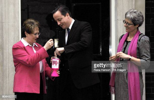 Prime Minister David Cameron places money in a donation box held by Pamela Goldberg chief executive of Breast Cancer Campaign and Laura Simons in 10...