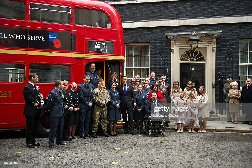 Prime Minister David Cameron poses for a photograph with members of the armed forces, The Poppy Girls and supporters of the Poppy Appeal outside Downing Street on November 7, 2013 in London, England. Prime Minister David Cameron welcomes a Poppy Bus and The Poppy Girls to Downing Street to support the Royal British Legion's Poppy Appeal.