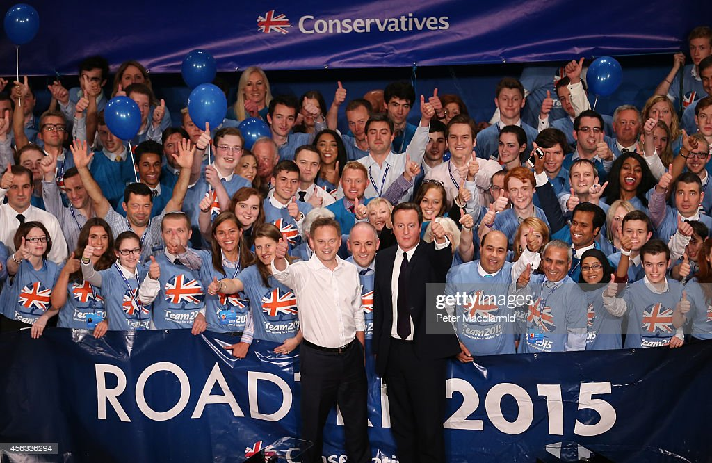 Prime Minister David Cameron poses for photographs with party chairman Grant Shapps and activists at the Conservative party conference on September...