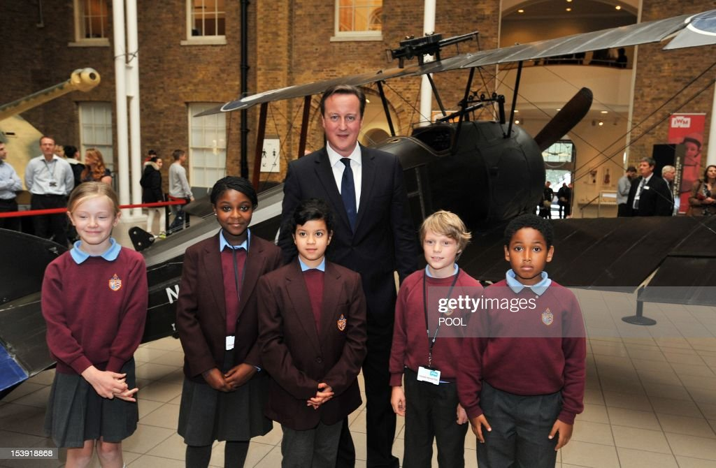 Prime Minister David Cameron (C) poses with schoolchildren as they stand in front of a Sopwith Camel by-plane at the Imperial War Museum in London on October 11, 2012 as he launches the start of World War one commemorations leading up the 100th anniversary of the outbreak of the war in 2014. Britain will stage events across the country and take thousands of children to visit the battlefields of World War I to mark the centenary of the conflict in 2014, Prime Minister David Cameron said. AFP PHOTO/POOL/ John Stillwell