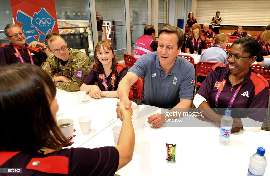 Prime Minister <a gi-track='captionPersonalityLinkClicked' href=/galleries/search?phrase=David+Cameron+-+Politician&family=editorial&specificpeople=227076 ng-click='$event.stopPropagation()'>David Cameron</a> sits and talks to a group of Olympic volunteers, as he met some of the huge volunteer workforce at the ExcCel venue in Docklands on Day 12 of the London 2012 Olympic Games on August 8, 2012 in London, England.