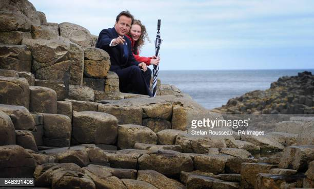 Prime Minister David Cameron sits in the 'Wishing Chair' on the Giant's Causeway in County Antrim with Mel McQuity of the National Trust