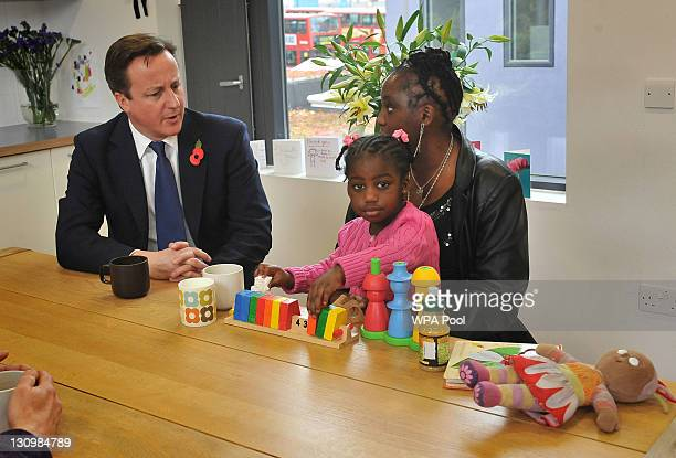 Prime Minister David Cameron speaks with adoptive mother Karen McKellar and her adoptive twoyearold daughter Angel during a visit to the Archway...