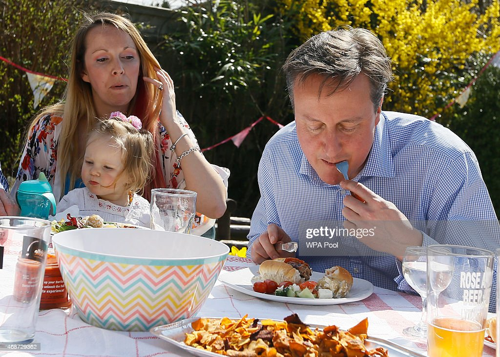 Prime Minister David Cameron speaks with Lilli Docherty and her daughter Dakota, as he has lunch with people who have benefited from tax and pension changes that come into force, in a garden on April 6, 2015 near Poole, England. Britain goes to the polls for a general election on May 7.