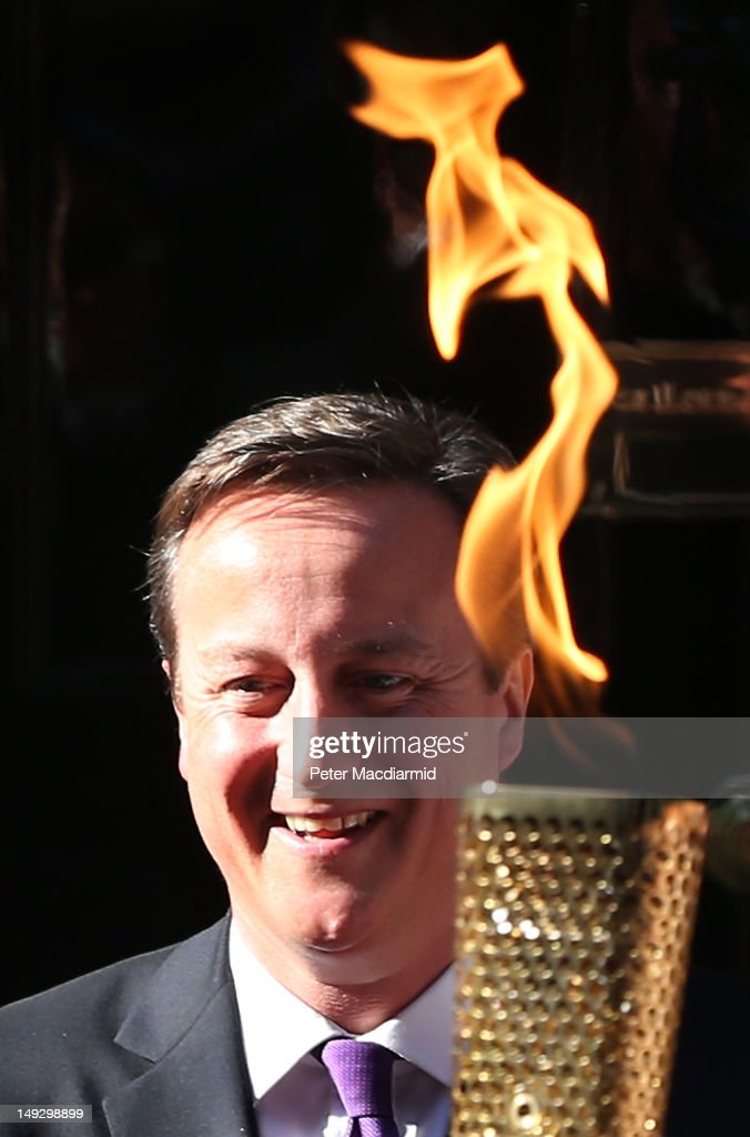 Prime Minister <a gi-track='captionPersonalityLinkClicked' href=/galleries/search?phrase=David+Cameron+-+Politician&family=editorial&specificpeople=227076 ng-click='$event.stopPropagation()'>David Cameron</a> stands next to an Olympic torch in Downing Street on July 26, 2012 in London, England. The torch relay will end tomorrow with it's arrival at the Olympic Park for the opening ceremony of the London 2012 Games.