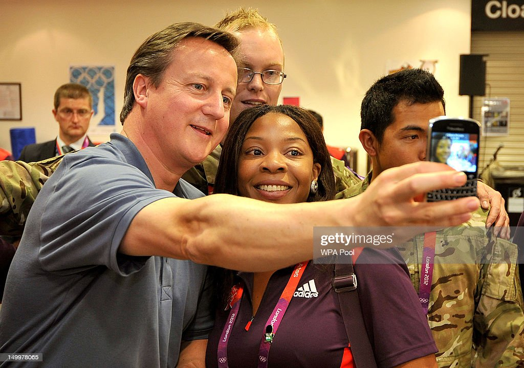 Prime Minister <a gi-track='captionPersonalityLinkClicked' href=/galleries/search?phrase=David+Cameron+-+Politician&family=editorial&specificpeople=227076 ng-click='$event.stopPropagation()'>David Cameron</a> takes a photo with Olympic volunteer Anita Akuwudike on her Blackberry phone, as he met some of the huge volunteer workforce at the ExcCel venue in Docklands on Day 12 of the London 2012 Olympic Games on August 8, 2012 in London, England.