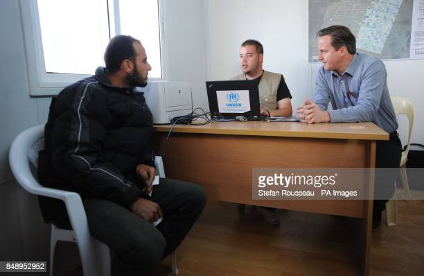 Prime Minister David Cameron talks to a refugee from Syria in the reception centre at the Za'atri refugee camp near the Syrian Jordanian border where...