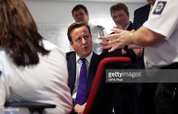 Prime Minister David Cameron talks to UK border agency officials in their control room during a visit to Heathrow terminal 5 on October 10 2011 in...
