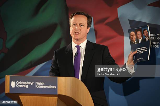 Prime Minister David Cameron visits holds up a copy of the Conservative Welsh manifesto as he speaks to supporters on April 17 2015 in Builth Wells...