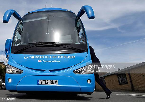 Prime Minister David Cameron walks back onto his Conservative Party campaign bus after a factory visit whilst campaigning in Pendle on May 1 2015 in...