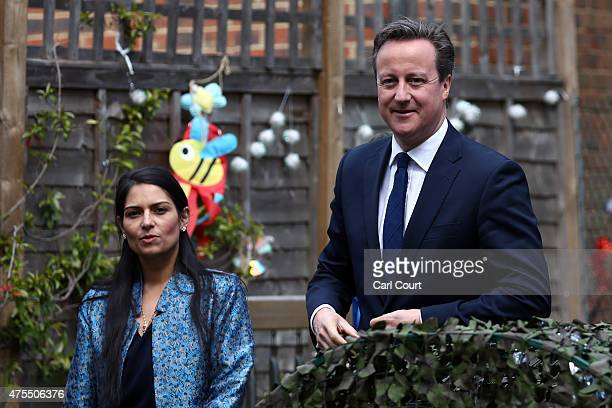 Prime Minister David Cameron walks with Employment Minister Priti Patel during a visit to a children's nursery on June 1 2015 in London England The...