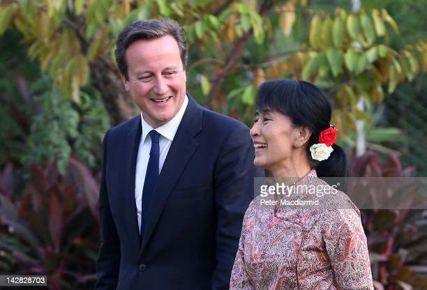 Prime Minister David Cameron walks with prodemocracy leader Aung San Suu Kyi in her garden on April 12 2012 in Yangon Myanmar Mr Cameron is ending...