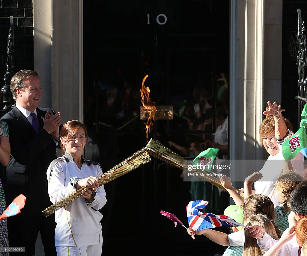 Prime Minister <a gi-track='captionPersonalityLinkClicked' href=/galleries/search?phrase=David+Cameron+-+Politician&family=editorial&specificpeople=227076 ng-click='$event.stopPropagation()'>David Cameron</a> (L) watches as Olympic torch bearer Kate Nesbitt (2-L) lights torches with Florence Rowe in Downing Street on July 26, 2012 in London, England. The torch relay will end tomorrow with it's arrival at the Olympic Park for the opening ceremony of the London 2012 Games.