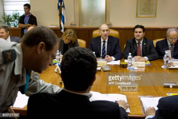 Prime Minister Ehud Olmert chairs the weekly cabinet meeting in his Jerusalem offices as Defense Minister Amir Peretz is briefed by a military...