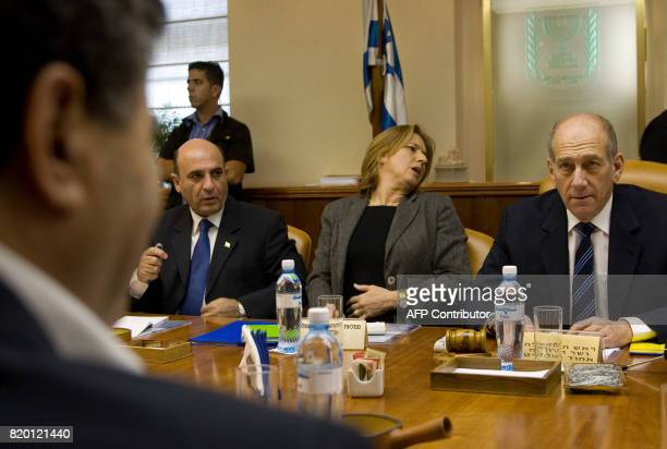 Prime Minister Ehud Olmert looks at his Defense Minister Amir Peretz as he chairs the weekly cabinet meeting 15 October 2006 in his Jerusalem offices...