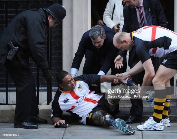Prime Minister Gordon Brown and rugby player Lawrence Dallaglio help up double amputee Derek Derenalagi after he fell on the doorstep of 10 Downing...