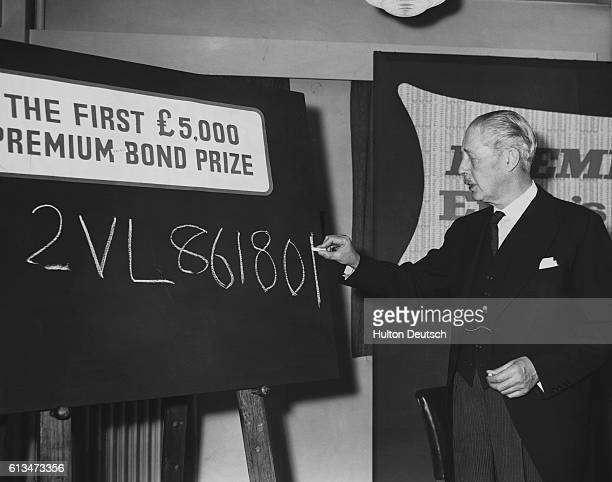Prime Minister Harold Macillan writes the number of the first premium bond ticket selected to win a prize 5 on a blackboard at the National Savings...