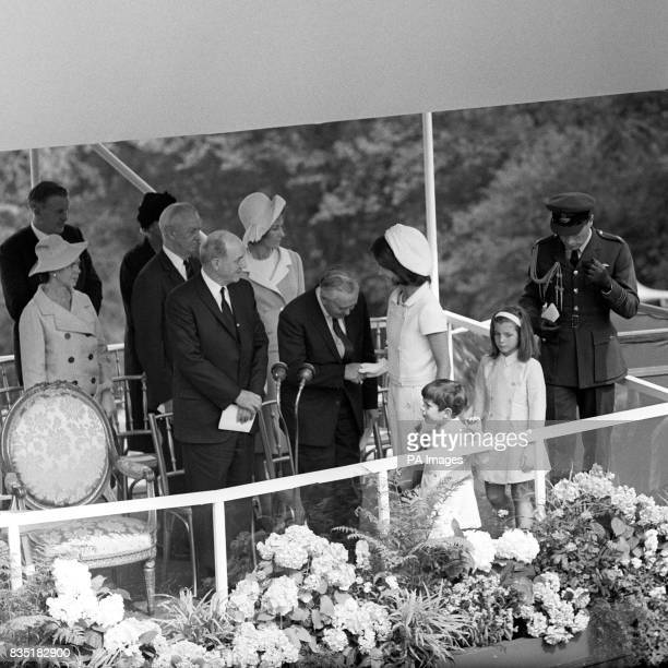 Prime Minister Harold Wilson bows as he shakes hands with Jacqueline Kennedy as she arrives on the dais with her children Caroline and John for the...