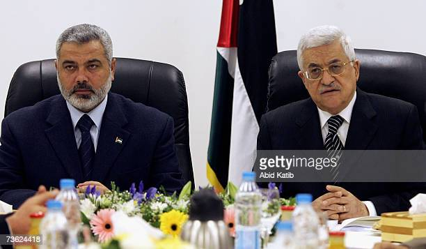 Prime Minister Ismail Haniya and Palestinian President Mahmoud Abbas chair the first meeting of the new Palestinian unity government bringing...
