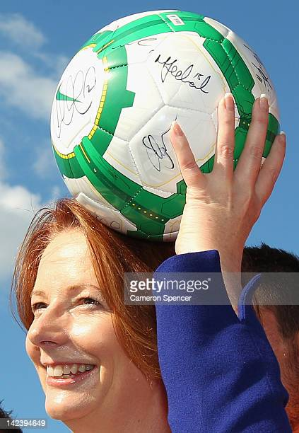 Prime Minister Julia Gillard places a football on her head during a press conference to announce the inclusion of a Western Sydney team for the...
