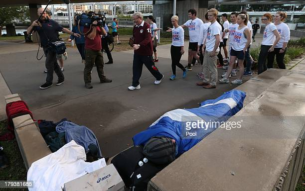 Prime Minister Kevin Rudd and supporters walk away after posing for a group photo unaware that a homeless man slept nearby on a bench during an early...
