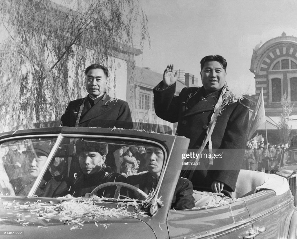 Prime Minister Kim Il Sung (right) of Communist North Korea and Chinese Premier Zhou Enlai wave to crowds after arriving in Beijing on a state visit.