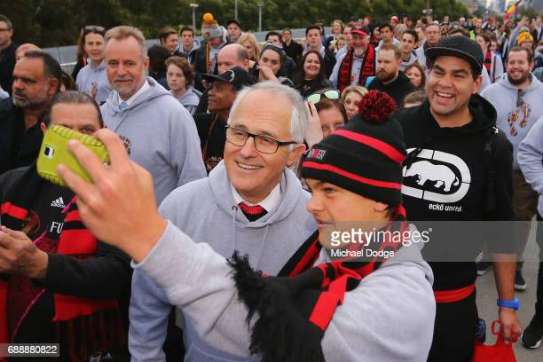 Prime Minister Malcom Turnbull poses with a Bombers fans during The Long Walk before the round 10 AFL match between the Richmond Tigers and the...