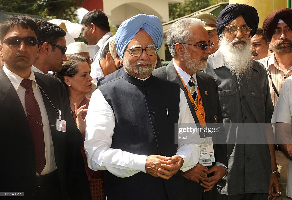 Prime Minister Manmohan Singh of India (C) and Chairperson of India's UPA government Sonia Gandhi (3L) walk with officials as they arrive to attend the 2011 ICC World Cup second Semi-Final between India and Pakistan at Punjab Cricket Association (PCA) Stadium on March 30, 2011 in Mohali, India.