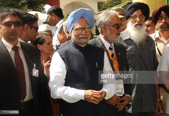 Prime Minister Manmohan Singh of India and Chairperson of India's UPA government Sonia Gandhi walk with officials as they arrive to attend the 2011...