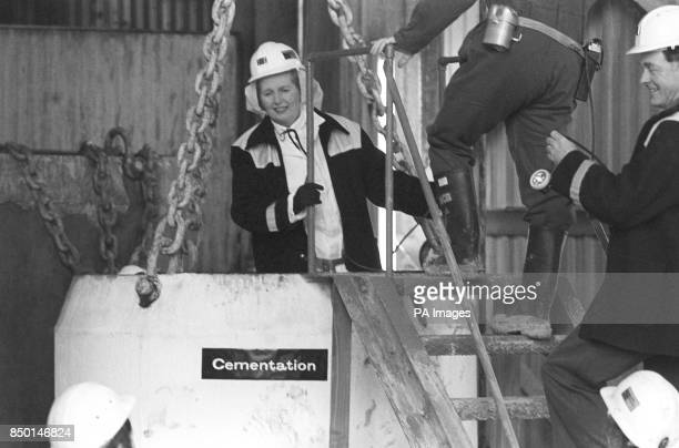 Prime Minister Margaret Thatcher clad in white overalls a miner's helmet and donkey jacket inside a five ton 'kibble' a large steel bucket suspended...