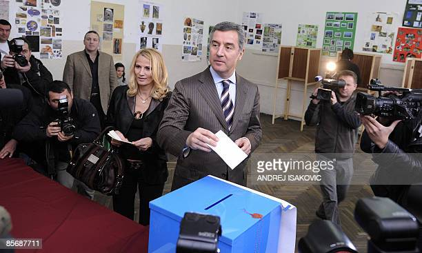 Prime Minister Milo Djukanovic of the ruling Democratic Party of Socialists accompanied by his wife Lidija prepares to cast his ballot at a polling...