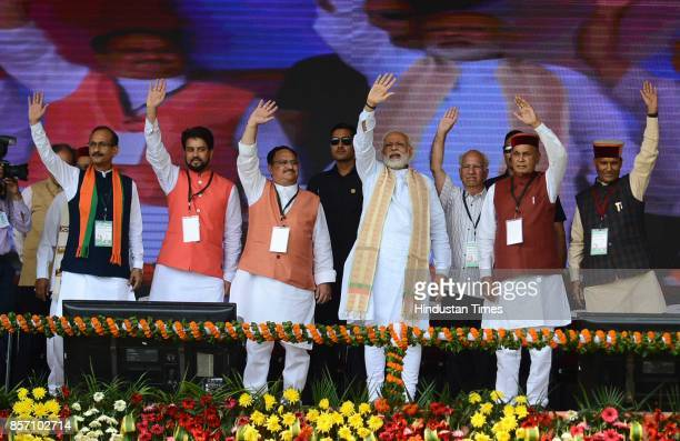 Prime Minister Narendra Modi along with BJP leaders greets the people during a BJP Abhar Rally at Luhnu ground on October 3 2017 in Bilaspur India PM...