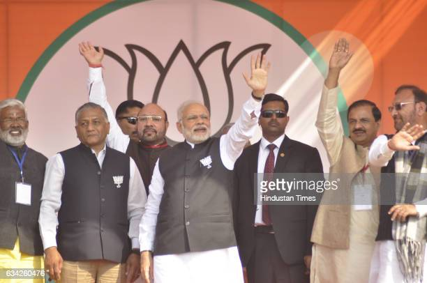 Prime Minister Narendra Modi along with Union Ministers Mahesh Sharma VK Singh and other BJP leaders waves hand to greet the supporters during a BJP...
