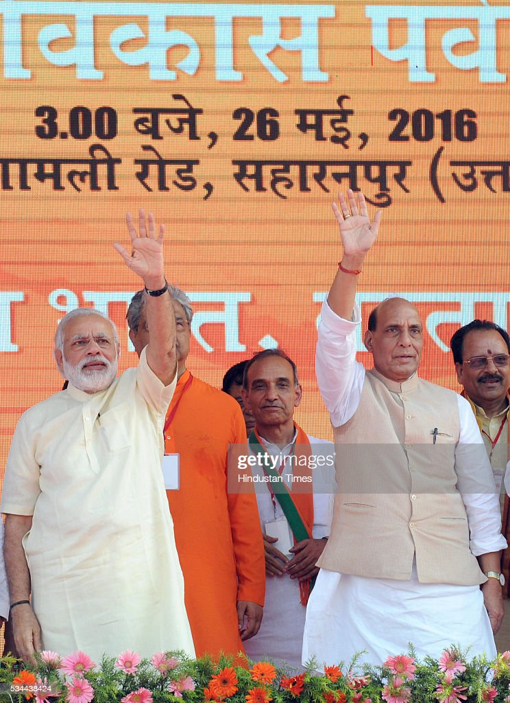 Prime Minister Narendra Modi and Home Minister Rajnath Singh waving at the crowd at a rally to mark the second anniversary of the formation of his government at the centre, on May 26, 2016 in Saharanpur, India. Prime Minister Narendra Modi's speech to mark two years of his government focused on farmers and the poor at a massive rally in Saharanpur in Uttar Pradesh, where crucial assembly elections will be held early next year.