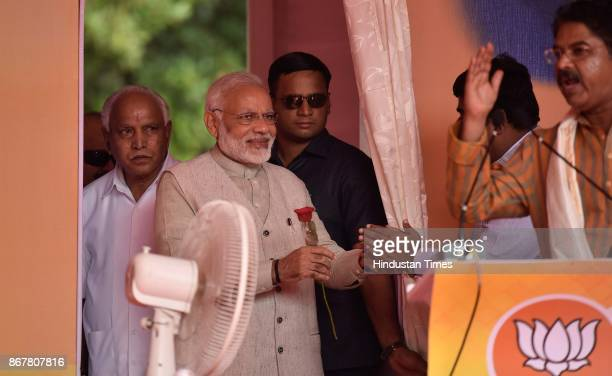 Prime Minister Narendra Modi arrives to address the BJP party workers during a public meeting for the launch of various programmes outside HAL...