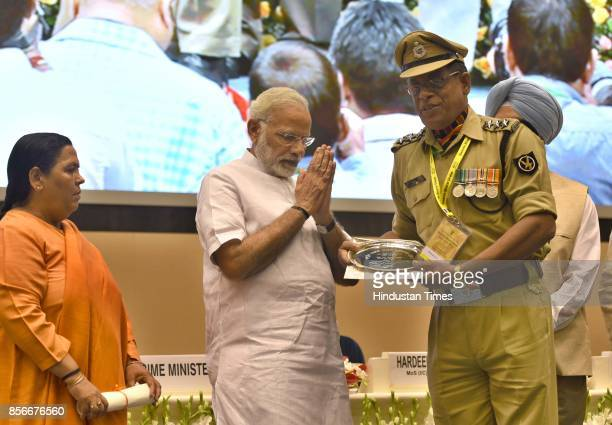Prime Minister Narendra Modi gives away the prizes to the winners as Uma Bharti looks on during the 3rd anniversary of Swachh Bharat Mission and the...